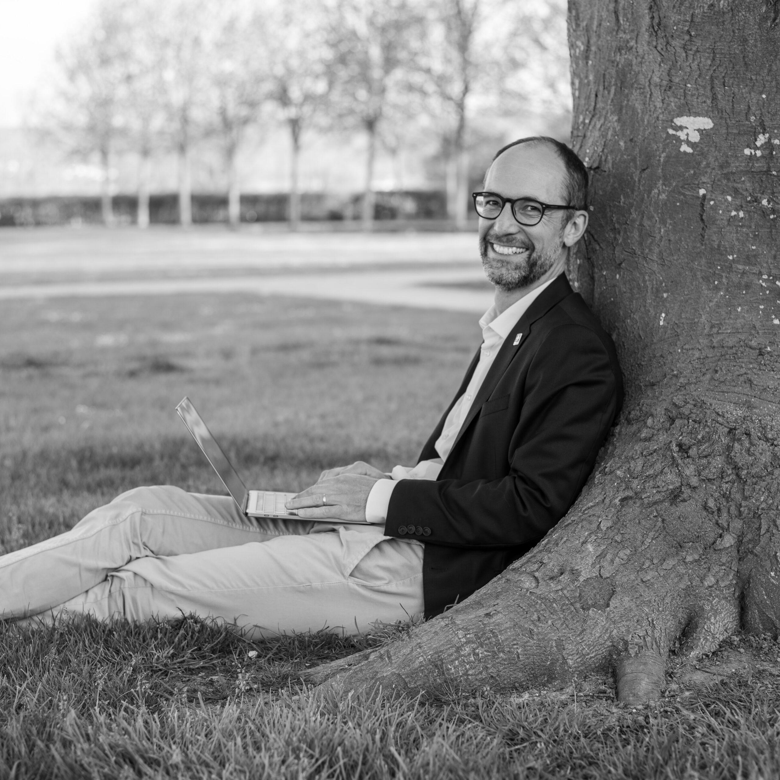 Foto von Sebastian Hueber mit Laptop an einen Baum gelehnt
