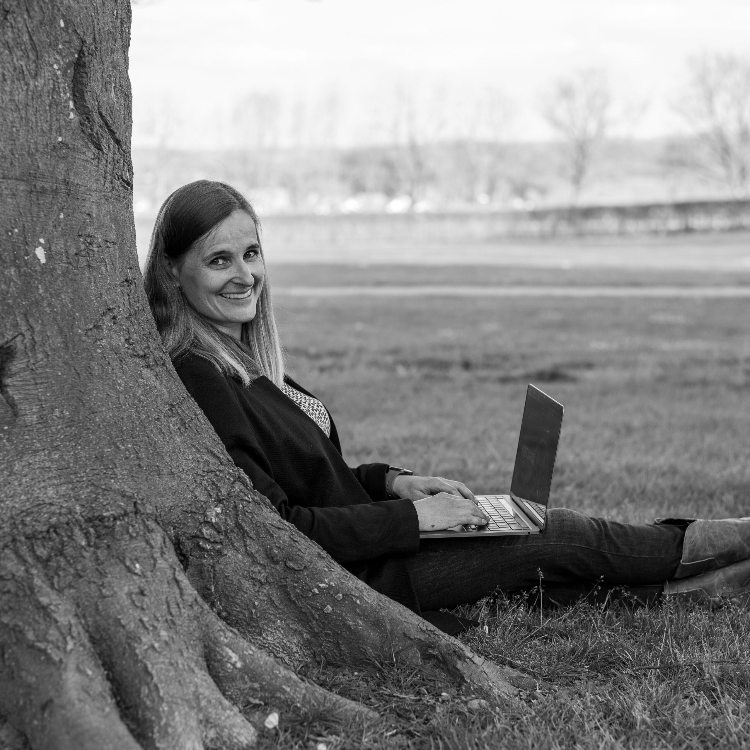 Franka Theile Hueber mit einem Laptop an einen Baum angelehnt